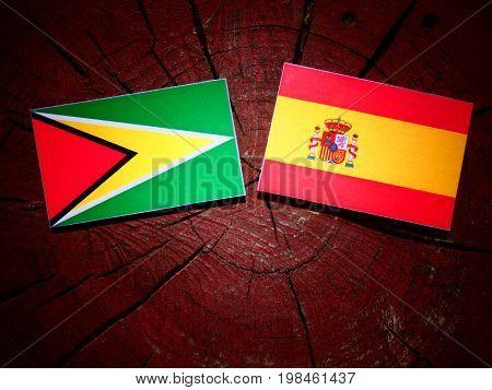 Guyana Flag With Spanish Flag On A Tree Stump Isolated