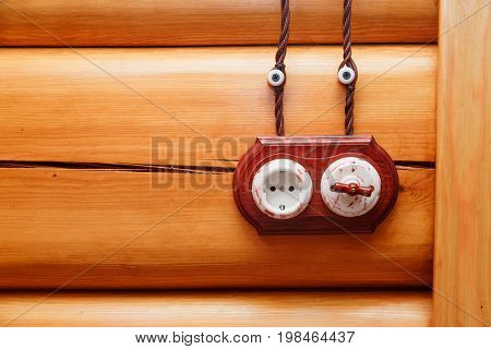 Electrical socket and switch in retro style on a wooden wall. Design of electricians in the house