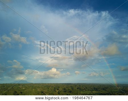 Cloudy skyscape with rainbow. Landscape aerial view with colorful rainbow