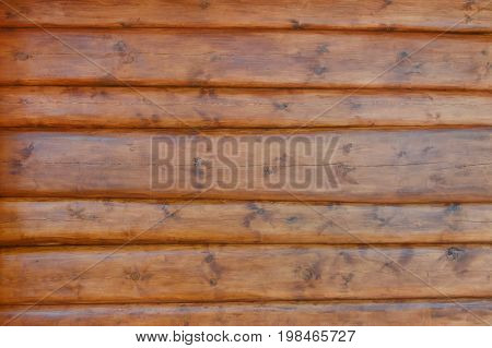 The texture of the wall of the house is made of round logs, covered with protective impregnation. Close up