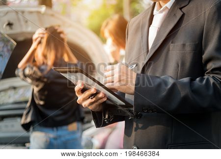 Side view of writing on laptop while insurance agent examining car after accident