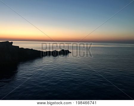 Rugged coastline silhouette sunset