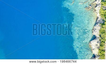 Aerial photo above coastline land sea reef crystal clear blue water
