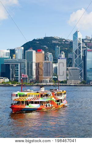HONG KONG - JULY 10 2017: A colorful Star Ferry approaches a ferry terminal at Tsim Sha Tsui in Hong Kong. The city's iconic Star Ferry carries passengers across Victoria Harbor between Hong Kong Island and Kowloon since 1888.