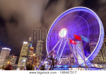 HONG KONG JULY 10 2017: Long exposure of the spinning Observation Wheel at Hong Kong's Central Pier near Victoria Harbour with the downtown financial district in the background.