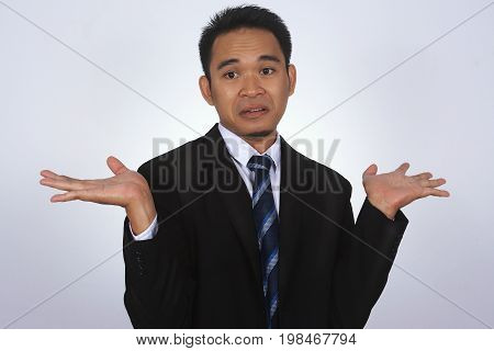 Photo image of a handsome attractive young Asian businessman with i don't know gesture isolated on white