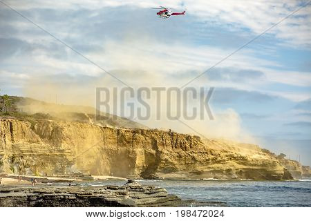 Us Coastguard Helicopter In Flight With Clouds Of Dust