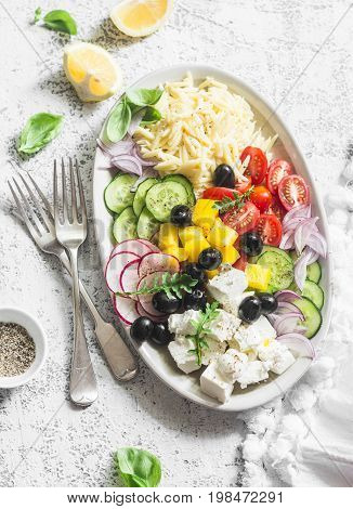 Feta orzo tomatoes cucumbers radishes olives peppers salad on a light background top view. Healthy food concept. Mediterranean food style