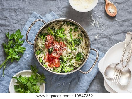 One pot orzo primavera. Orzo pasta with asparagus broccoli green peas and cream in a saucepan. On a light background top view
