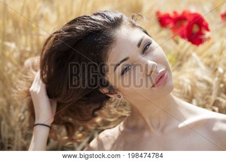 Portrait of a young brunette woman on a background of golden wheat field, summer outdoors