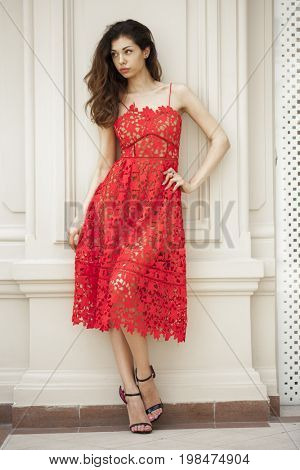 Portrait in full growth, Beautiful young brunette woman in red dress, against gray wall, indoor