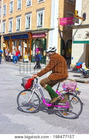 Salzburg, Austria - May 01, 2017: Men wearing traditional Austrian costume riding a bicycle at street on sunny day at Salzburg, Austria on May 01, 2017