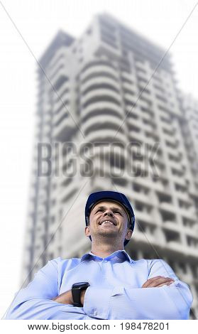Engineer working on a building site wearing a protective helmet standing on the building background. Engineering and architecture concept.