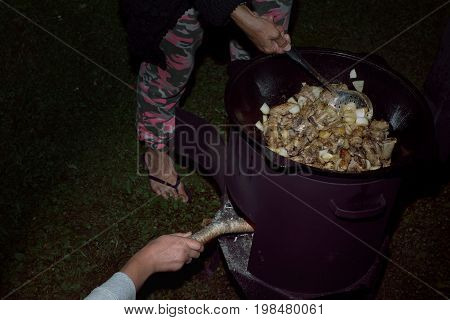 People cooking together fried vegetables and meat in the cast iron pot night scene