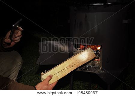 Man keeping fire under a cast iron pot using mobile as a torch night scene