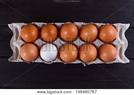 Container of ten eggs. Nine eggs brown one egg white. on black wooden background. Eggs container