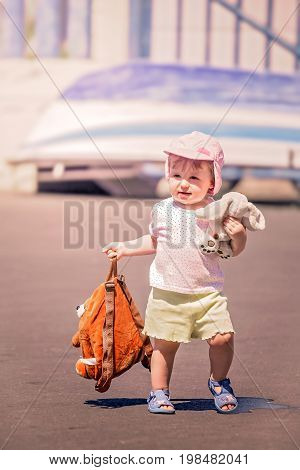 Little cute girl going on holiday carrying her doggy backpack and favourite plush teddy bear toy, La Gomera island, Canary Islands, Spain