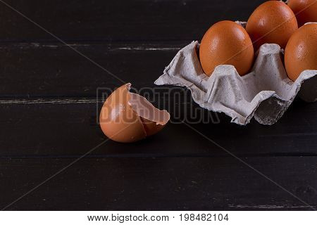 Cardboard egg box And eggshell shells on black wooden background. Eggs container