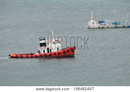 Tugboat at the port entrance color image selective focus horizontal image