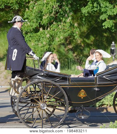 STOCKHOLM SWEDEN - JUN 06 2017: The swedish princess and prince Sofia and Carl Philip Madeleine and Chris Bernadotte smiling and waiving to the audience from the royal coach on their way to celebrate the swedish national day.