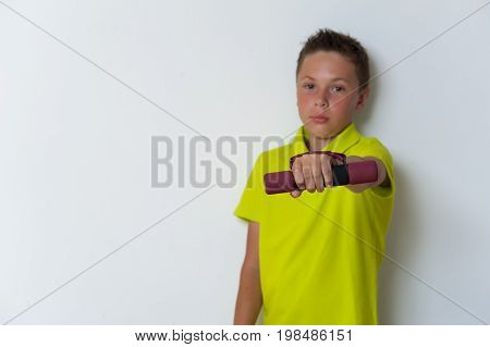 Portrait of fit tween child posing with dumbbell over white background. Healthy lifestyle and fitness