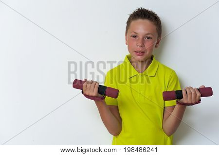 Smiling caucasian tween child doing biceps exercise with dumbbells, posing on white background, looking at the camera. copyspace. Healthy lifestyle and fitness