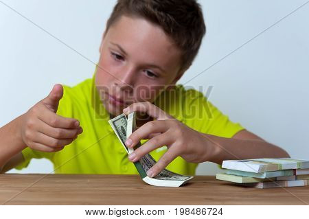 Portrait of tween caucasian boy sitting at the table and counting dollar bills.