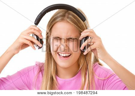 face expression contest-teenage girl screaming with headphones over white background