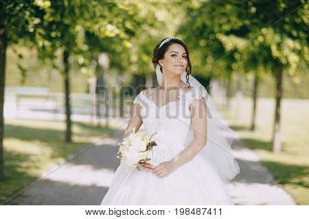 beautiful bride in a magnificent white dress and a crown on his head standing in a park and holding a bouquet of flowers in hand