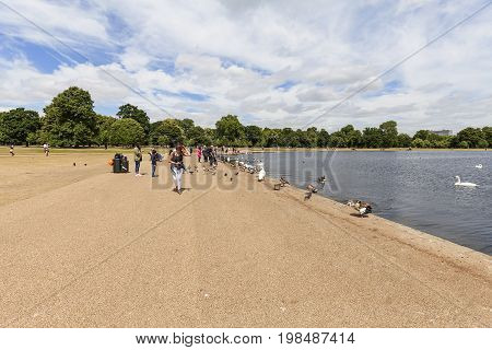 LONDON UNITED KINGDOM - JUNE 23 2017: Long Water pond in Kensington Gardens in front of Kensington Palace tourists.The private gardens of Kensington Palace are among the Royal Parks of London cover an area of 270 acres
