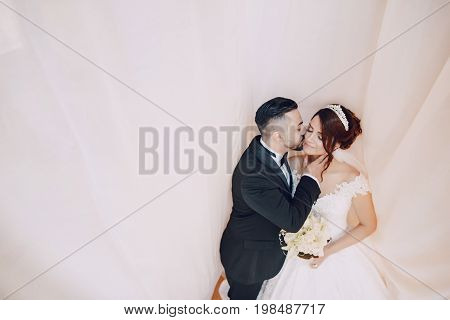A beautiful young Turkish man wearing a black suit and a beard standing near tulle along with his beautiful bride in a white dress and a bouquet of flowers
