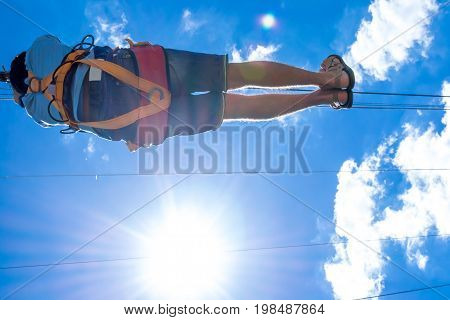 Ukraine Migea - June 30 2017: Zipline. A view of a man sliding on a steel cable against a beautiful blue sky with white clouds. Extreme and active rest.