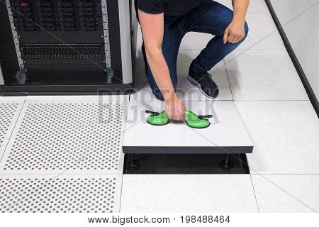 Low section of male computer engineer lifting floor tile using vacuum suction cups in datacenter