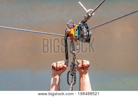 Zipline. Equipment for safe sliding on steel cable. Woman's hands close-up during the flight.