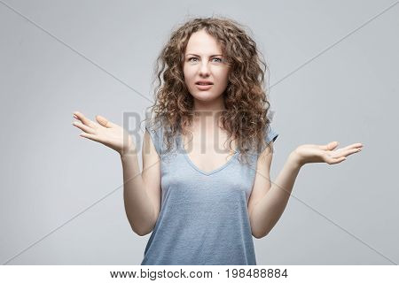 Unsure confused doubtful European woman with long curly hair in grey casual t-shirt shrugging shoulders in questioning gesture of uncertainty and keeping mouth openedhaving confused clueless look.