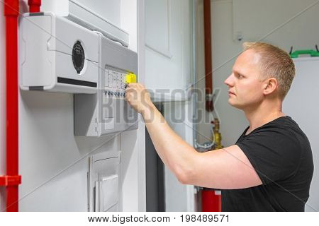 Confident mid adult male IT technician opening fire panel in data center