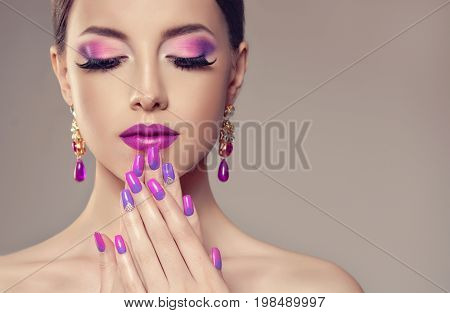 Beautiful girl model with fashion violet make-up and purple design manicure on nails . Jewelry and cosmetics , large violet earrings