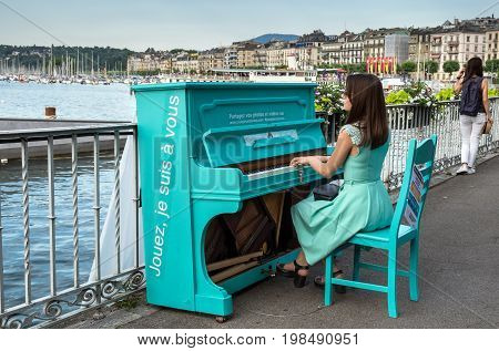 GENEVA SWITZERLAND - JUNE 24 2017: Elegantly dressed undefined girl play on piano on embankment on Geneva Lake