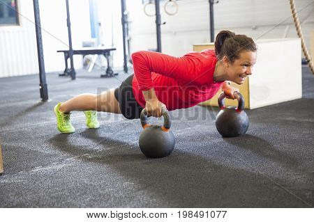 Full length of determined woman doing pushups on kettlebell in health club