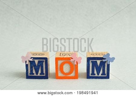 Mom spelled with alphabet blocks decorated with small bows