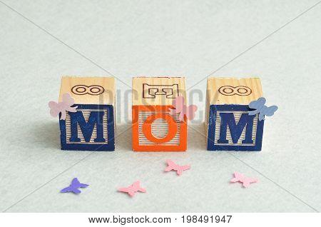 Mom spelled with alphabet blocks decorated with small bows and butterflies