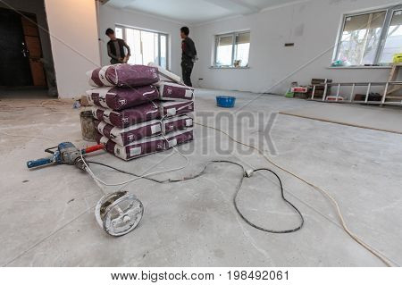 Interior of apartment with new windows materials ( bags of cement or concrete) and handle concrete mixer on the floor during on the renovation overhaul and construction ( preparing concrete by workers )
