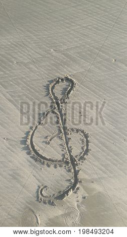 Treble clef drawn in sand on the beach