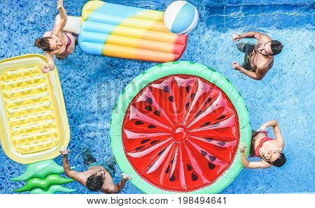 Happy friends playing with ball inside swimming pool - Young people having fun on summer holidays vacation - Travelholidaysyouthfriendship and tropical concept - Seasonal color tones filter