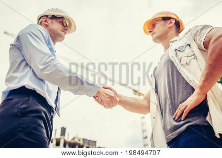 Architect engineer shaking hands other hand at construction site. Business teamwork, cooperation, success collaboration concept.