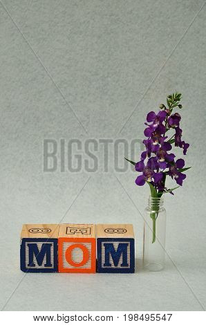 Mom spelled with alphabet blocks and small purple flowers