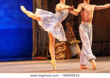 ballet, love, theater concept. dance duet of two persons, ballerina like porcelain statuette standing on one stretched toe and holding on to her tough male partner