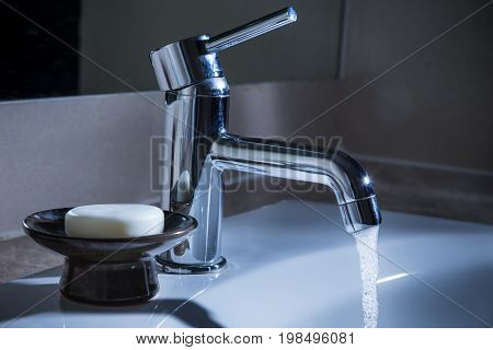 bathroom water faucet with water running at night concept for waste resouce