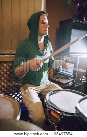 Drummer in recording studio playing drums. Music band rehearsal before live concert