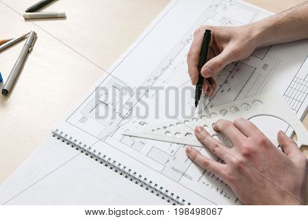 Architecture scheme with unrecognizable hands drawing on desktop of designer workplace